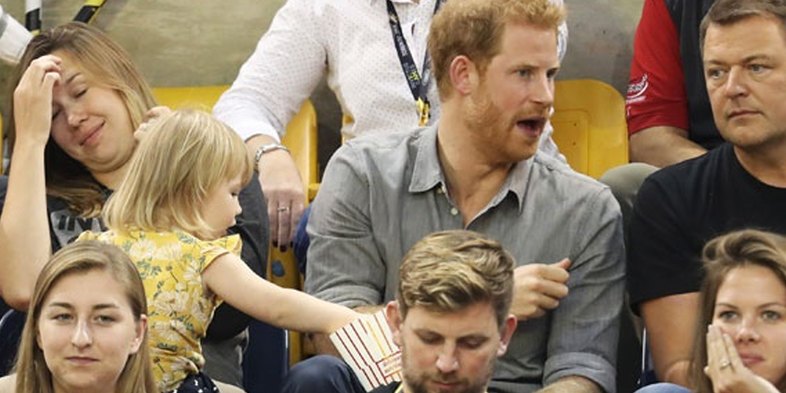 This toddler sneaking popcorn from Prince Harry is all of us